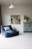 Blue velvet easy chair next to child's painting and chest of drawers