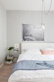 Poster mit Wolken über dem Bett im pastellfarbenen Schlafzimmer
