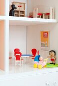 Retro dolls' furniture in white cabinet converted into dolls' house