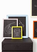 Children's drawings on blackboards with colourful frames on top of black cabinet