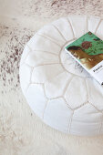 Book on white leather pouffe on white cowhide rug
