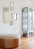 Various retro mirrors on wall above old leather pouffe