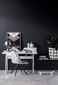 Grauer Stuhl und Schreibtisch vor schwarzer Wand
