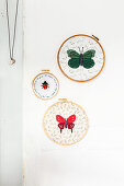 Fabric embroidered with butterflies and ladybird in embroidery frames