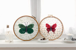 Fabric embroidered with butterflies in embroidery frames on windowsill