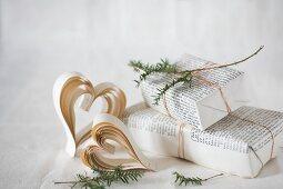 Herzen aus Papier und in Buchseiten eingepacktes Geschenk