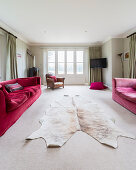 Cowhide rug between two red sofas in living room