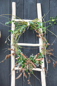 Wreath of Cornus, Ilex and various cones on ladder