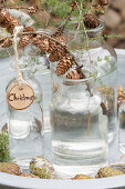 Glass jars decorated for Christmas (larch sprigs with cones, wooden decoration)