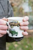 Hands holding mug with car motifs