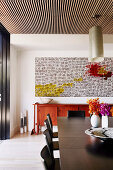Large abstract painting above the red sideboard in the dining room