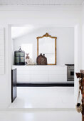 View of white kitchen unit with antique gold frame mirror and cage