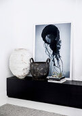 Antique clay pot and vintage olive wood basket in front of modern art on lowboard