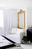 Armchair with white cover, gold frame mirror and white, floor-length curtain in the bedroom