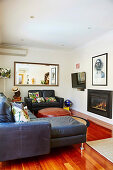 Leather furniture, fireplace, TV and wall mirror in the living room