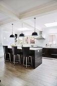 Middle block with bar stools in front of a kitchenette in an open kitchen with porcelain floor tiles in a wood look