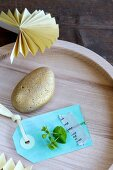 Gold-painted pebble and paper tag in wooden dish