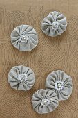 Small fabric rosettes with beads on piece of painted cardboard