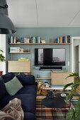 Fernseher und Wandregal an blauer Wand im Wohnzimmer