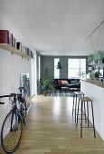 Fahrrad und Küchentheke im offenen Wohnraum mit Wohnzimmer