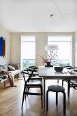Schwarze Stühle am Esstisch mit bodentiefen Fenstern
