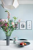 Blumenstrauß in Rosatönen auf dem Esstisch vor hellblauer Wand