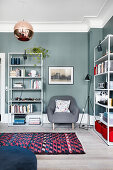 Simple shelves against petrol-blue walls in living room