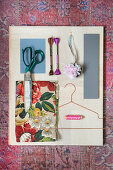 Mood board of floral fabric and wooden sewing utensils
