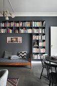 Day bed frames by bookshelves on grey wall