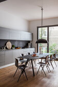 Modern dining set in large, grey fitted kitchen with balcony