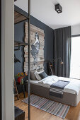 Bedroom in shades of grey with artwork painted on wooden boards above bed