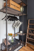 Old trunk and wooden crate on industrial-style clothes rack