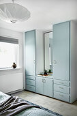 Old fitted cupboards with pale blue doors in bedroom