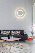 Circular lamp on wall above grey sofa and retro coffee tables