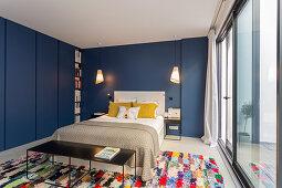 Blaue Wände und Einbauschränke im Schlafzimmer mit Fensterfront