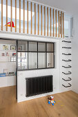 Wall-mounted ladder rungs leading to mezzanine in child's bedroom