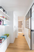Shelves and fitted cupboards in hallway with wooden floor