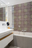 Patterned tiles above bathtub in small bathroom