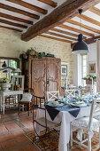 Festlich gedeckter Esstisch vor antikem Holzschrank in rustikalem Wohnraum mit Terrakottafliesenboden und Holzbalkendecke