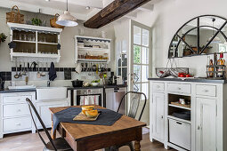 White cupboards, table and two chairs in rustic kitchen