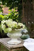 Antike Pflanzenschale mit weißen Hortensien auf Holztisch im Garten