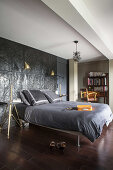 Double bed against black wall relief in bedroom