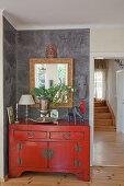 Rote Kommode im Asiastil mit Ethno-Accessoires vor grauer Wand