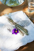 Old silver cutlery and pebbles wrapped in lace on stacked napkins