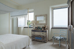 Shabby-chic chest of drawers in white and blue bedroom with sea view