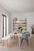 Dining table, shell chairs and bench next to balcony doors and in front of wall-mounted shelves