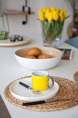 Yellow mug on plate on raffia place mat on breakfast table
