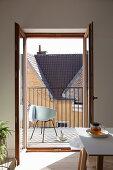 Blick durch geöffnete Flügeltür auf Balkon mit Schalenstuhl