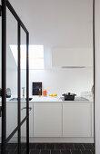 Blick durch geöffnete Glastür in weiße Einbauküche