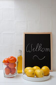 Citrus fruits, bottle of oil and Welcome sign against white wall tiles in kitchen